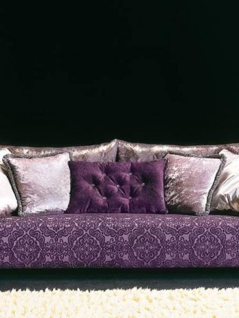 Three seater sofa with purple fabric covering